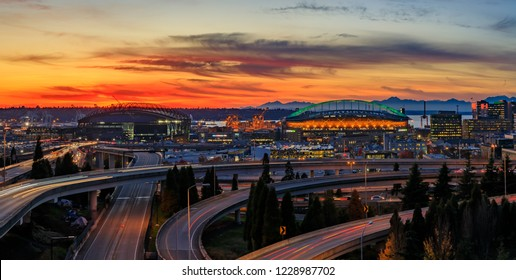 Panorama of Seattle downtown skyline beyond the I-5 I-90 freeway interchange at sunset with long exposure traffic trail lights from Dr. Jose Rizal or 12th Avenue South Bridge