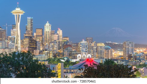Panorama Seattle downtown skylines, urban office buildings with Mt Rainier at blue hour as seen from Kerry Park.