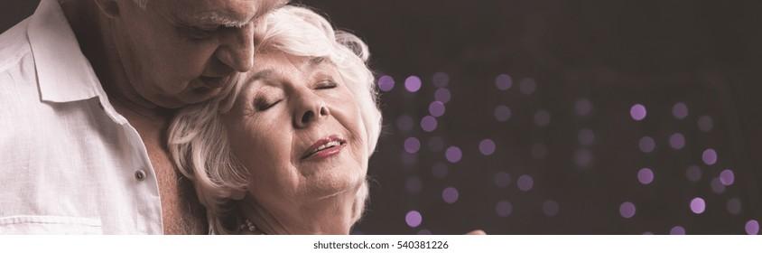 Panorama of senior elegant man embrancing elderly woman with bookeh background