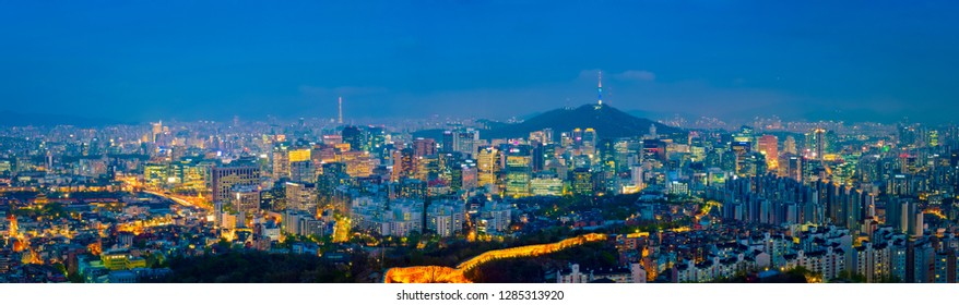 Panorama of Seoul downtown cityscape illuminated with lights in the evening view from Inwang mountain. Seoul, South Korea.