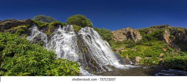 panorama of the Shaki Waterfall with a rainbow, height of 18 m. It is located in Syunik Province, Armenia. Dramatic bluff rocks