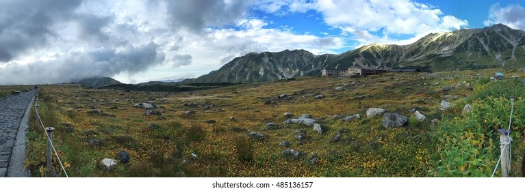 Panorama shot of Mount Tateyama with a grass and flower field and trekking road at Murodo, Japan, as part of the Alpine Route. September, 2016.
