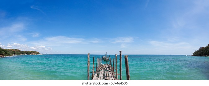 Panorama shot of old wood pier lie into the nice blue sea, a great view for vacation to relax mind and body from hard work
