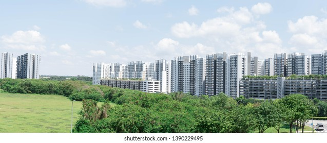 Panorama shot of residential HDB condominiums in Singapore. Green forest park and blue sky with clouds