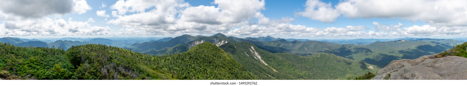 Panorama shot from the summit of the Ghotics Mountain on a sunny day. Beautiful view of the forest, valleys and many peaks. Shot in the Adirondacks National Park, NY, USA.