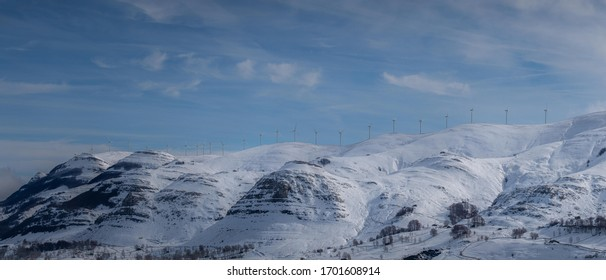 Panorama shot of windmills in a snowed mountain with blue sky.