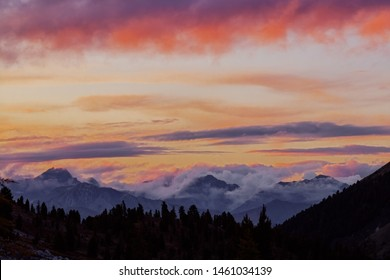 Panorama silhouette forest and mountain tops in red orange blue clouds gradient sunset