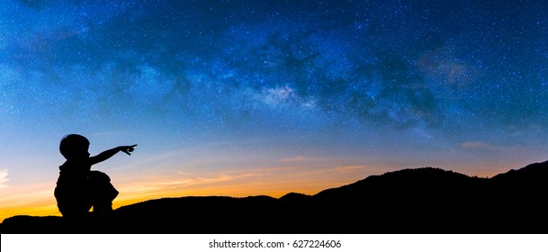 Panorama silhouette image of Happy boy point finger to the milky way in sky with mountain in background on sunset time.