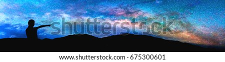 Panorama silhouette image of Happy girl stand and point finger to the milky way on sky with mountain in background on sunset time.