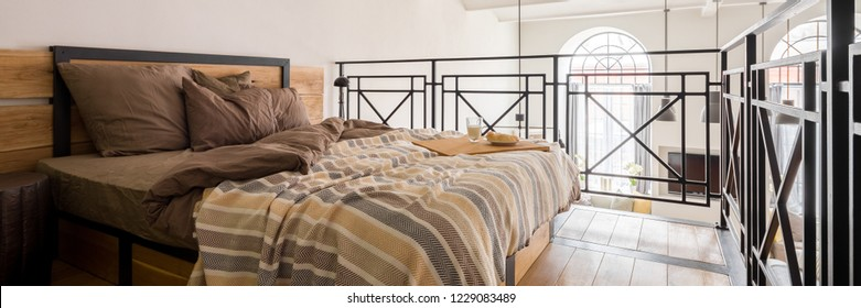 Panorama of simple mezzanine bedroom with double bed