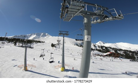 Panorama of ski resort, slope, people on the ski lift, skiers on the piste at high altitude mountain summit