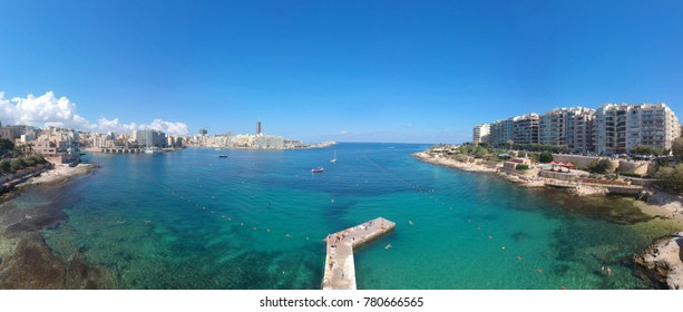 Panorama Sliema, view from bird's-eye view, flight on the drone. Busy summer beach at Exiles Beach and Bay with Independence Gardens behind, off St Julians Bay and Tower Road Sliema, Malta