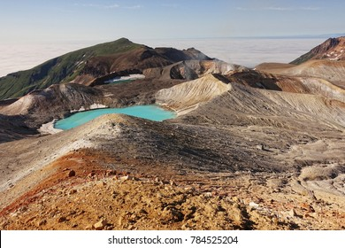 Panorama of the slope of Ebeko volcano on Paramushir Island. Acid lake in the crater of the volcano and the top of the mountain behind the strait covered by fog. Kuril Islands, Russia