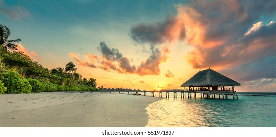 Panorama of small island resort in Maldives, Indian Ocean at sunset. Holidays destination