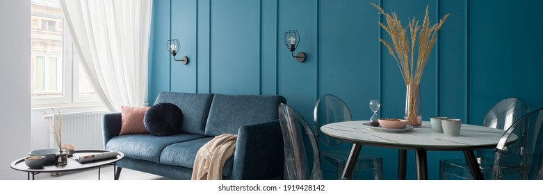 Panorama of small and nice designed living room with modern dining table and stylish blue wall with molding