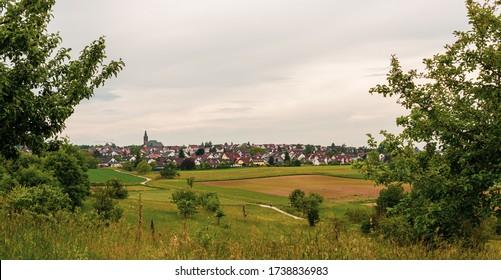 Panorama d'une petite ville. Une petite ville de Bavière. Maisons dans la vallée. Champs et pâturages. Un chemin de gravier parmi les champs. Photo de la colline.