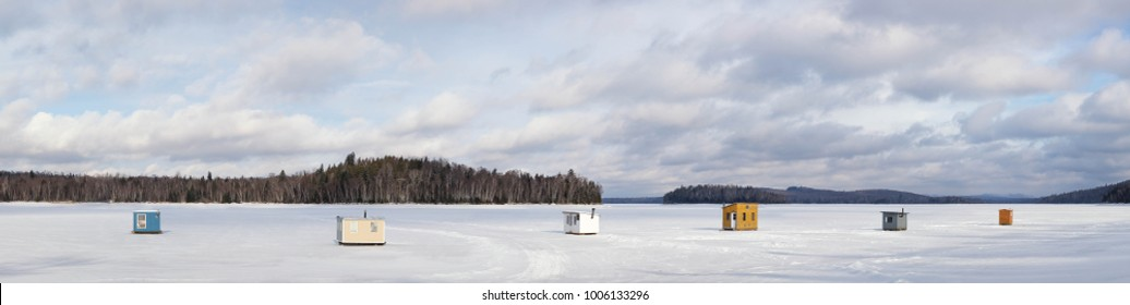 Panorama of small wooden shelters for ice fishing installed on a frozen lake with trees and sky in the background