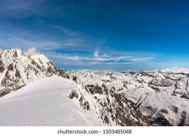 Panorama of snow covered Italian Alps from Pointe Helbronner in the Mont Blanc massif on the watershed between France and Italy, with the moon in the blue sky