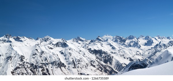 Panorama of snow covered mountains with mount Elbrus at background. View from region Dombay, Caucasus Mountains in winter.