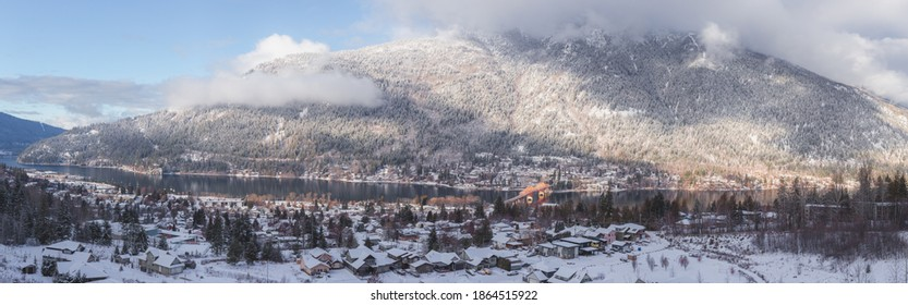 Panorama snow covered winter view of Nelson, B.C. Canada along the West Arm of the Kootenay Lake with snowy mountain backdrop.