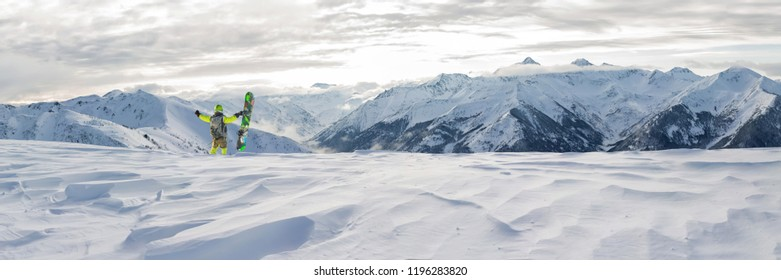 panorama snowboarder freerider is standing in the snowy mountains in winter under the clouds