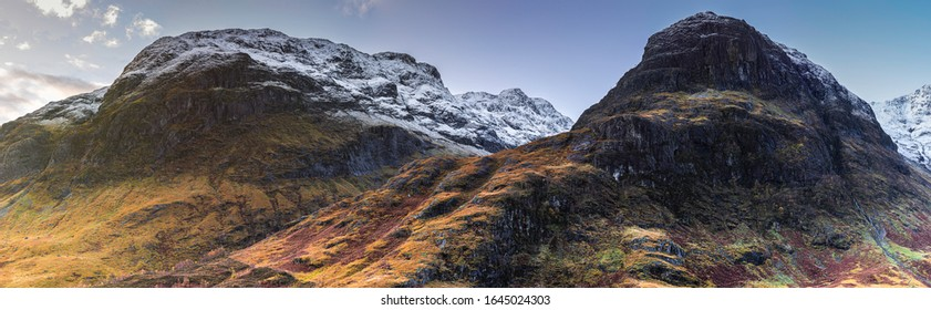 Panorama of snowcapped mountain range on sunny autumn morning in Glencoe, Scottish Highlands,UK.Mountain peaks covered with snow and sunlight in valley below.Majestic landscape of Scotland.