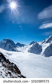 panorama of snow-covered slopes and peaks and the sun with rays and glare.zimny landscape - Shutterstock ID 1010389573