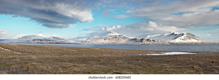 Panorama of snowy mountains in Iceland with some yellow grass and a lake in front of them.