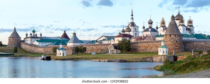 Panorama of the Solovetsky monastery with blue sea bay in the foreground at sunset, temples, towers, surrounding wall on Bolshoy Solovetsky Island, Russia