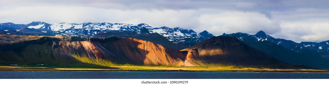 Panorama of the southern coastline of the Snaefellsnes peninsula in Iceland illuminated by warm evening sunlight, Iceland.