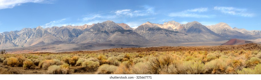 Panorama of the southern tip of the Sierra Nevada Mountains located in Central California under a clear blue sky with wispy white clouds.