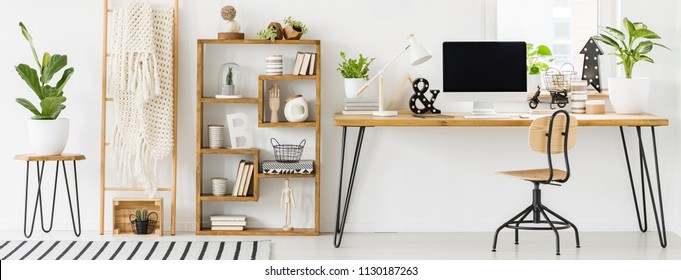 Panorama of a spacious home office interior with a bookcase with decorations next to a desk with a computer and white lamp. Real photo