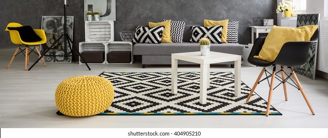 Panorama of a spacious modern living room arranged in scandinavian style, furnished in grey and white with yellow elements