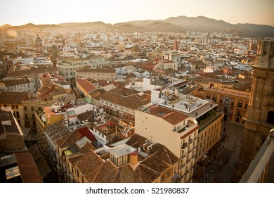 Panorama of the spanish city Malaga, brown and yellow buildings in the sunset sky