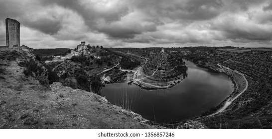 Panorama of Spanish landscape with medieval castles and river in cloudy day black and white