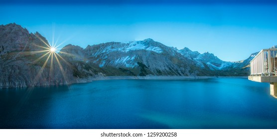 Panorama – the spectacular high alpine  Luner Lake (LunerSee). The backdrop off the snow-covered Austrian Alps, an awesome sunburst and the viewing gallery; add to the grandeur of this awesome image.