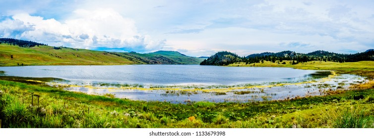 Panorama of Stump Lake surrounded by the Rolling Hills and wide open Grass Lands of the Nicola Valley along Highway 5A, between Merritt and Kamloops, British Columbia, Canada, under partly cloudy sky