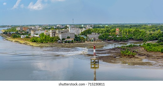 Panorama of suburb of Ho Chi Minh City on bank of Long Tau river with Tam Thon Hiep Temple with ancient symbol of good luck, Swastika (svastika), houses and navigation signs in Vietnam at low tide.
