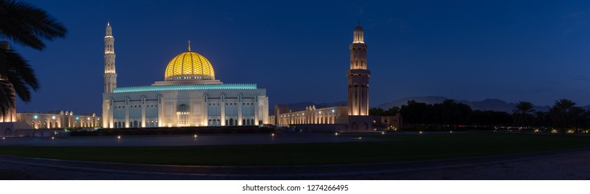 A Panorama of the Sultan Qaboos Grand Mosque in Muscat, Oman in the early evening hour showing off the dark blue sky and glowing dome.