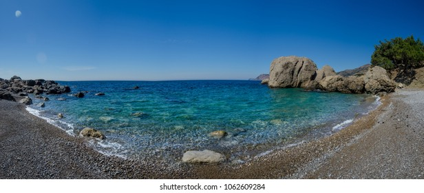 Panorama - a summer landscape with a beautiful sea and pebble beach - a sunny day in a wild bay in the rocks of Crimea, Sevastopol