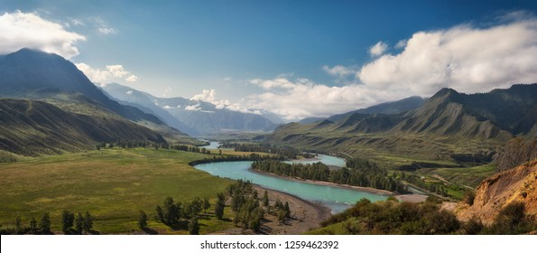 panorama of the summer landscape in the mountains. The valley of the mountain river Katun turquoise. the river flows between mountains and wide fields. blue sky and clouds view from high point