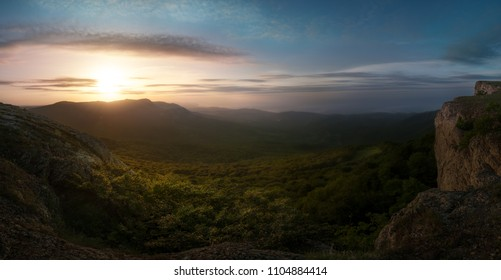 Panorama of summer sunrise in the mountains with a green valley and the sea in the background in warm tones - Crimea, view on the plateau Karabi with Tyrke