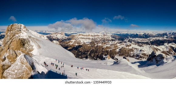 Panorama from the summit of Marmolada with skiers getting ready and Mount Sella on the background on a beautiful sunny day, Dolomites, Italy