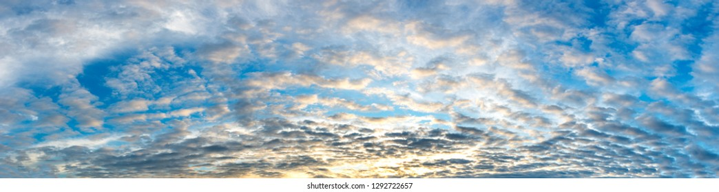 Panorama Sunlight with dramatic blue sky. Cumulus sunset fantasy clouds with sun setting down on dark background.Vivid orange cloud sky.