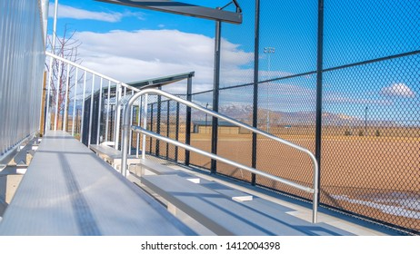 Panorama Sunlit bleachers overlooking a vast sports field on the other side of the fence