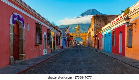 Panorama Sunrise in the Main Street of Antigua City with the Santa Catalina Arch and Agua Volcano, Guatemala.
