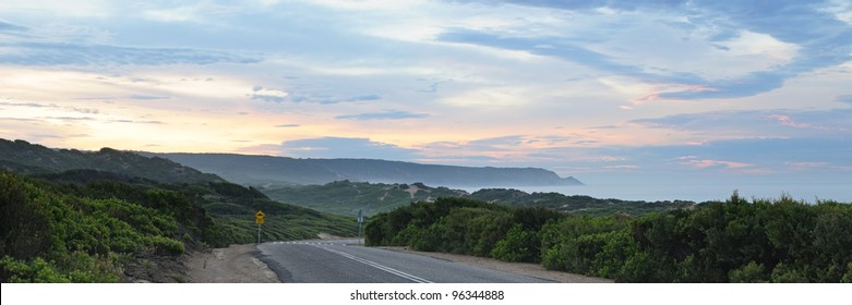 Panorama of sunrise at road to Guanamatta - surfing beach in Mornington Peninsula in cloudy morning when sun breaks through several cloud layers