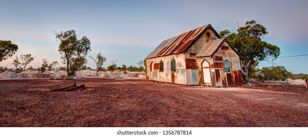 Panorama of sunrise at the rusty old church in Lightning Ridge Australia where the film Goddess of 1967 was filmed. Shot with sun behind the lens