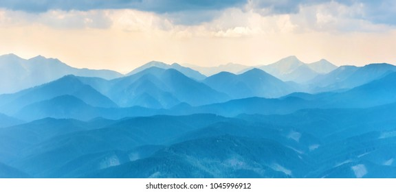 Panorama with sunset in blue mountains. Landscape view of peaks ridge