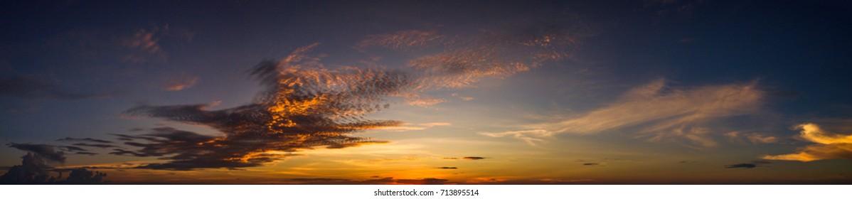 panorama Sunset with dramatic sky on dark background.Vivid sky on dark cloud.